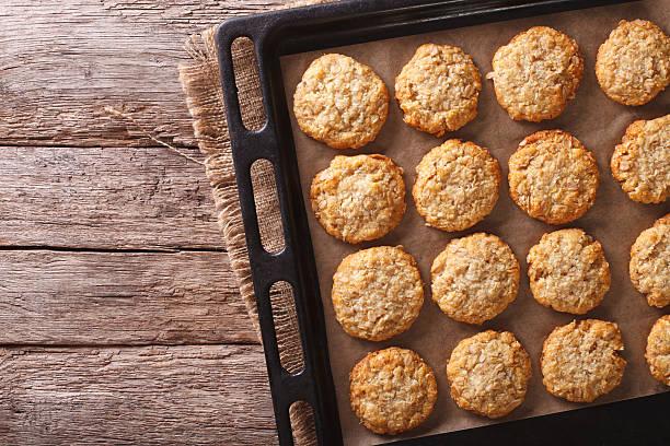 australian oatmeal cookies on a baking sheet. horizontal top view - bakplåt bildbanksfoton och bilder