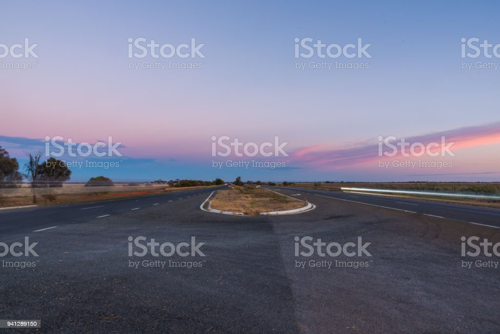 Australian outback landscape, multilane highway with colorful clouds at dusk. stock photo