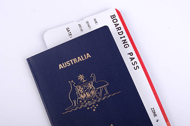 australian passport with international boarding pass - aeroplane ticket stock photos and pictures