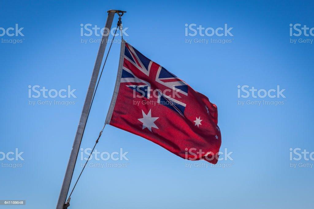 Australian Red Ensign flag on pole against blue sky background. stock photo