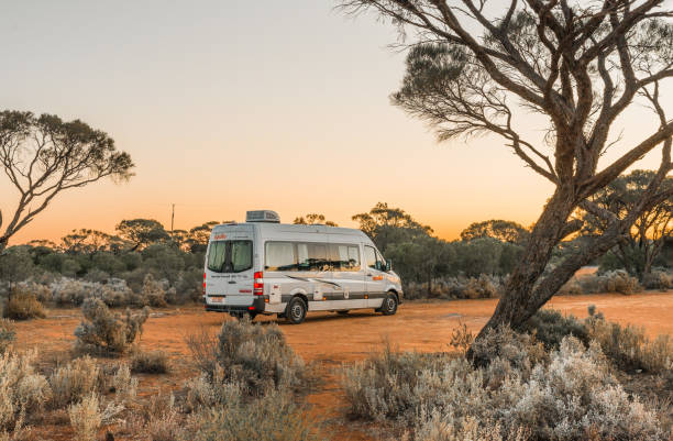 Australian rented motorhome stopped in at bush campgroung in Flinders Ranges region near Port Augusta at sunset. stock photo