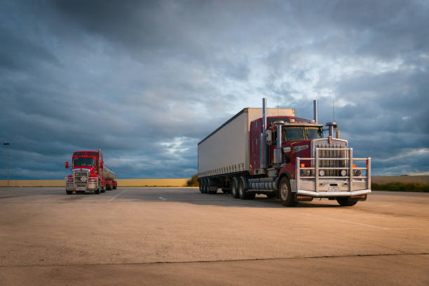 Australian road train trucks at service station rest area  off Western Highway near Ararat, Victoria at sunset with dramatic clouds stock photo