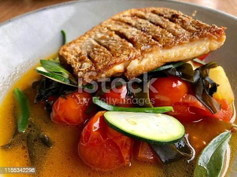 Aerial closeup of a piece of fresh sauted Australian Snapper Fish on a grey ceramic plate with cooked tomatoes and sliced zucchini with green native succulent leaf garnish