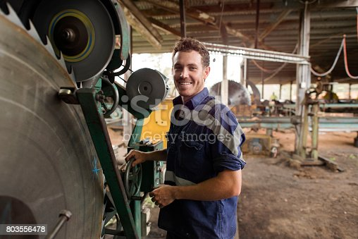 Portrait of a man smiling at camera using machinery