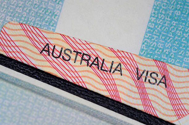 australian visa australian visa in between two british passport pages  passport stamp stock pictures, royalty-free photos & images