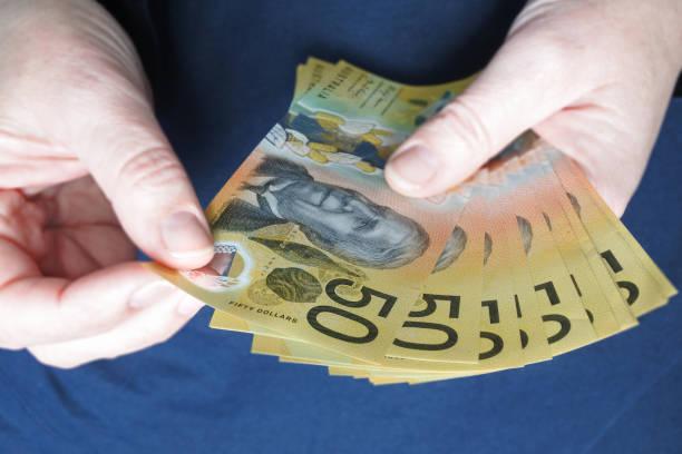 Australian woman counting Australian dollar banknotes stock photo