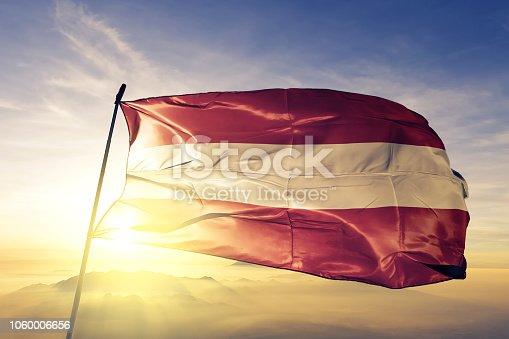 istock Austria Austrian flag textile cloth fabric waving on the top sunrise mist fog 1060006656