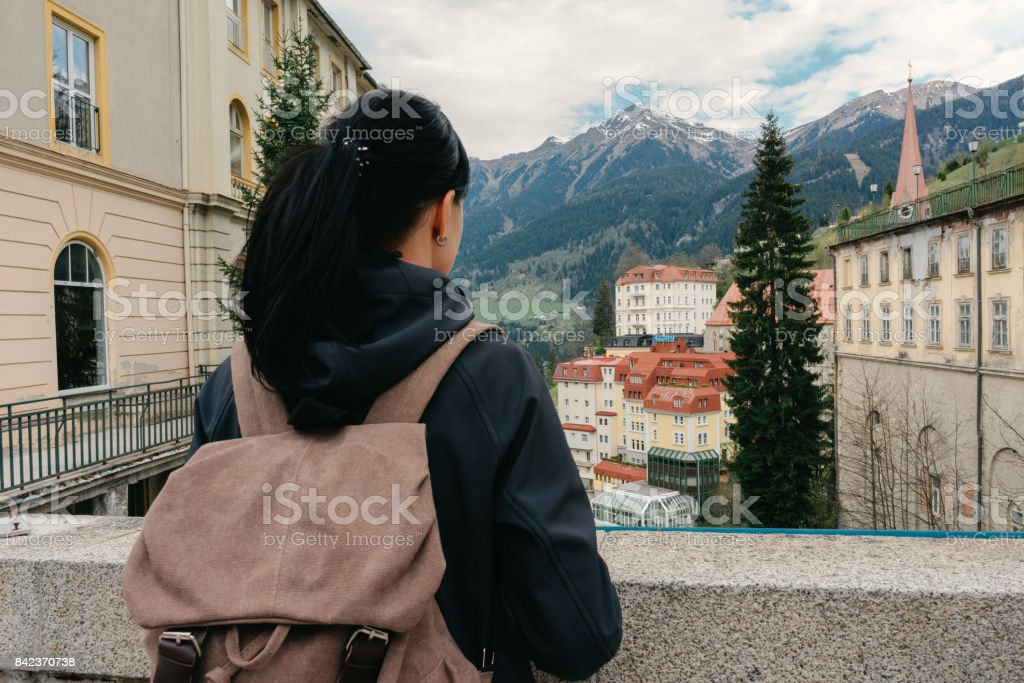 Austria. Bad Gastein. A traveler with a backpack is standing on a bridge overlooking the Alpine mountains stock photo