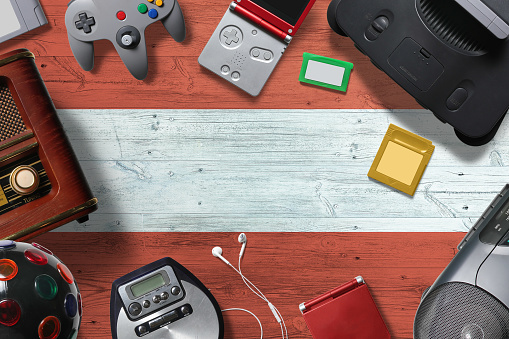Austria retro gaming concept. A collection of retro video game controllers shot from above on a national background.