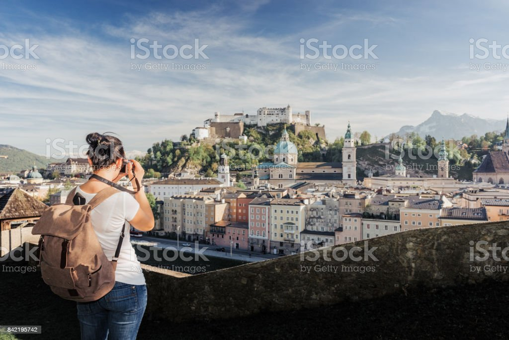 Austria. Salzburg. A young tourist girl takes pictures of the historic center of Salzburg: UNESCO World Cultural Heritage stock photo