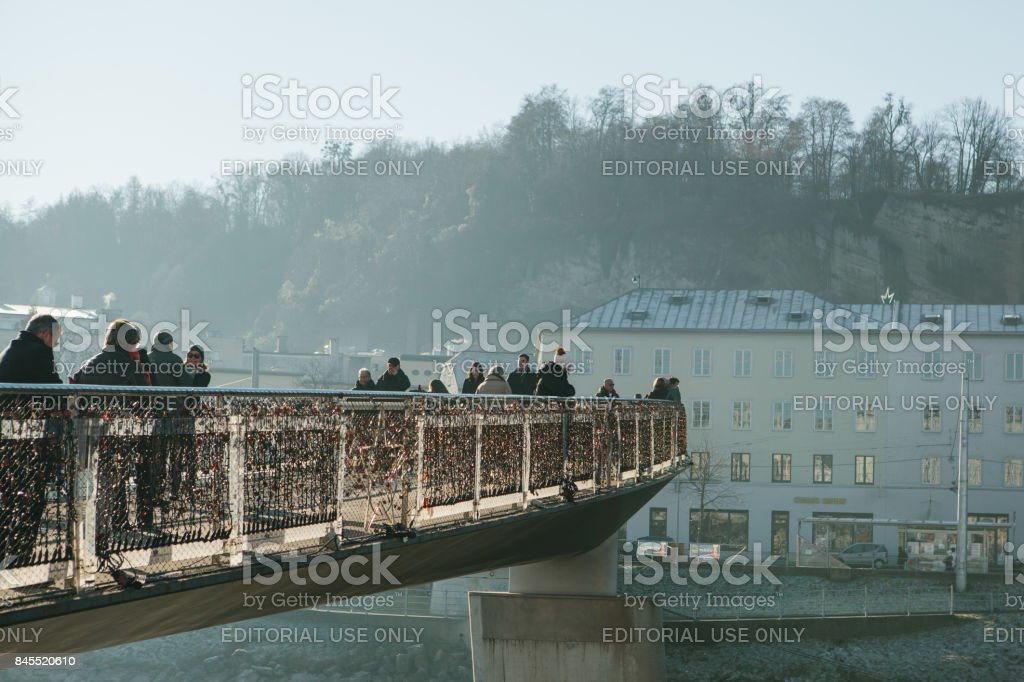 Austria, Salzburg, January 1, 2017: Mozart's pedestrian bridge connects the Old and New Towns. Pedestrians walk on the bridge. The hanging of locks on the bridge is a tradition. stock photo