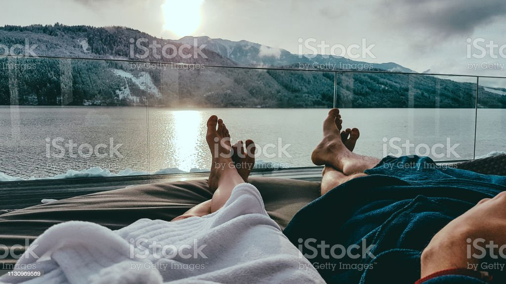 Austria-bathhouse Millstätter Lake Couple relaxing on the sun beds in Spa, Badehaus Millstätter See, Austria, by Millstätter See. Only the legs are visible and some parts of bathrobes. Snowy mountains in the back, snow on the terrace Adult Stock Photo