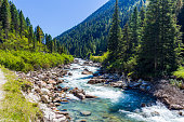 Austrian Alps. Starting famous Krimml waterfalls. Crystal clear water sparkles in the midday sun. Through the narrow creek wooden bridge spanned
