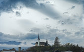 Austrian countryside landscape before thunderstorm. Cloudy sky and old church on hill