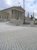 Vienna, Austria - December 9, 2016: Panorama of the Austrian Parliament Building. The building was built in 1874-1883 in the neo-Greek style by design of architect Theophil Hansen. The Athena Fountain in front of the building was designed by Theophil Hansen in 1870 and created in 1898-1902 by various sculptors. The building of Vienna Town Hall is visible on the right edge of the image.