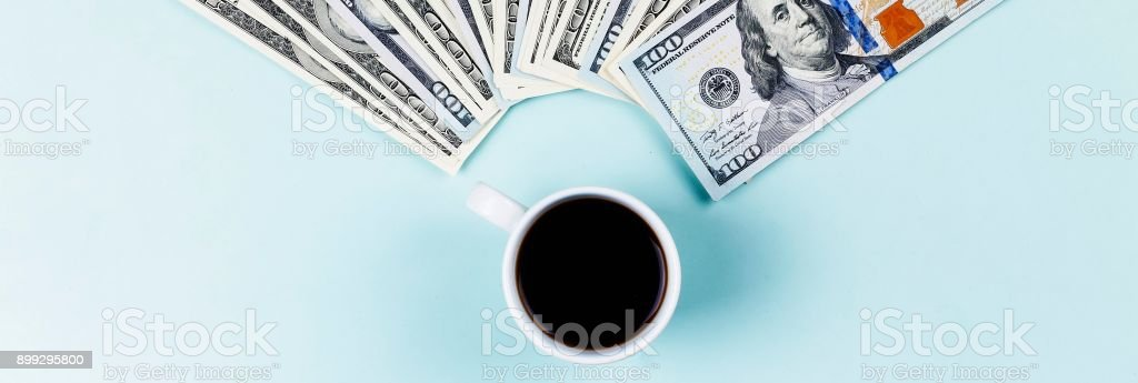 Authentic black coffee in a cup and US dollar banknotes stock photo