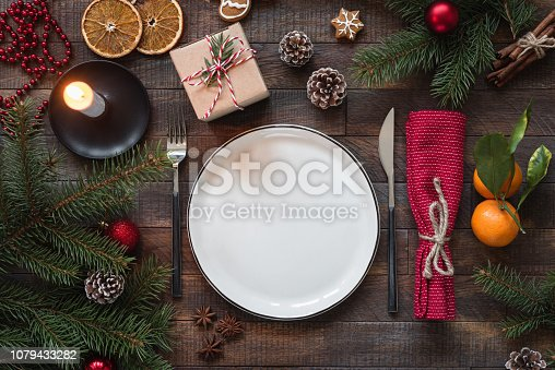 Authentic Christmas Table Setting. Empty Plate, Candles, Silverware, Fir tree, Gift boxes. Top view with copy space for text