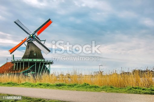 Full frame shot of authentic Dutch windmill with a dramatic cloudy sky and yellow grass