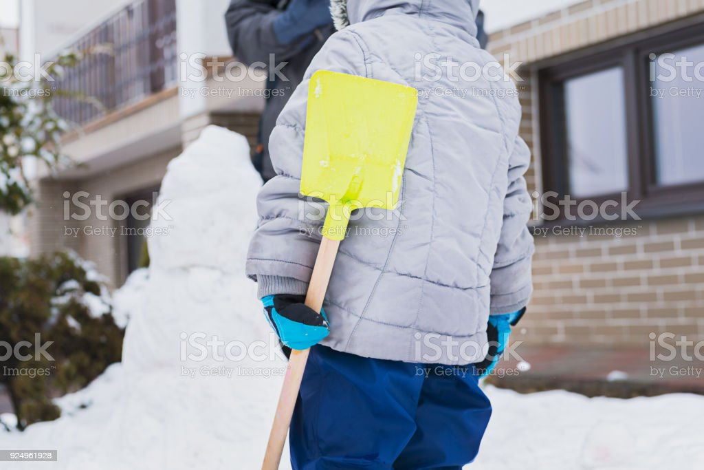 Authentic family winter fun. Family building a snowman in their front yard. Candid real people lifestyle image of making a snowman. stock photo
