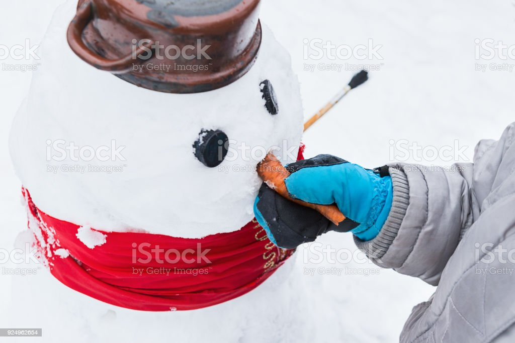 Authentic family winter fun. Young child building a snowman. Candid real people lifestyle image of making a snowman. Boy holding snowman by its carrot nose. stock photo