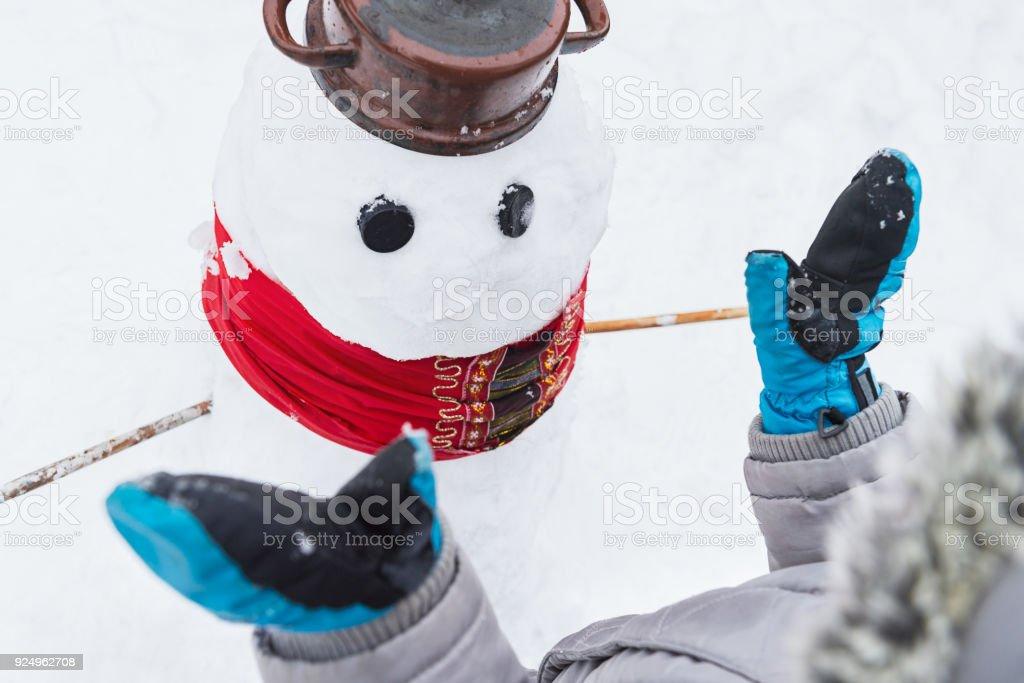 Authentic family winter fun. Young child building a snowman. Candid real people lifestyle image of making a snowman. stock photo