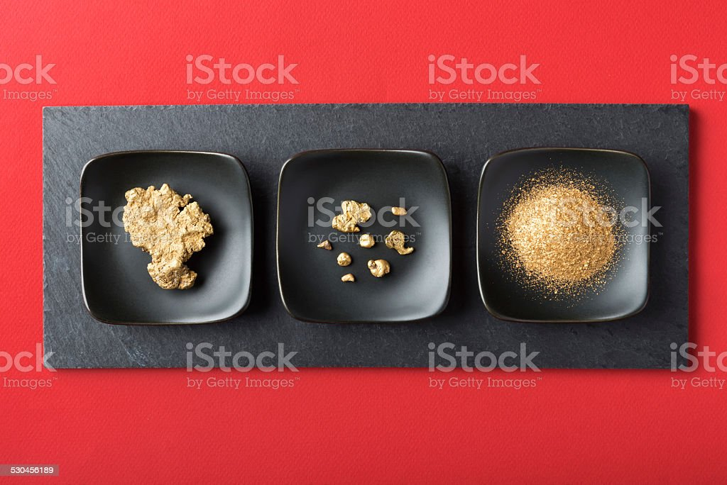 Authentic Gold Nuggets and Dust on Slate and Red Background stock photo