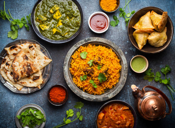 Authentic Indian dishes and snacks Top view of Indian traditional dishes and appetizers: chicken curry, pilaf, naan bread, samosas, paneer, chutney on rustic background. Table with choice of food of Indian cuisine, dinner/buffet naan bread stock pictures, royalty-free photos & images