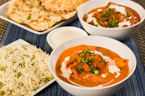 Authentic Indian Food Butter chicken curry, lamb vindaloo, basmati rice, nan bread and yoghurt raita naan bread stock pictures, royalty-free photos & images