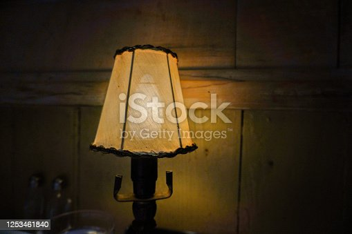 Classic table lamp with turned on bulb under lampshade is on table with cloth.  Authentic fine dining European atmosphere.