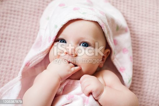Authentic portrait of 4 months baby girl wrapped in hooded towel after bath. Horizontal image in soft pink tones.