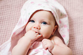 istock Authentic portrait of 4 months baby girl wrapped in towel after bath. 1205387879