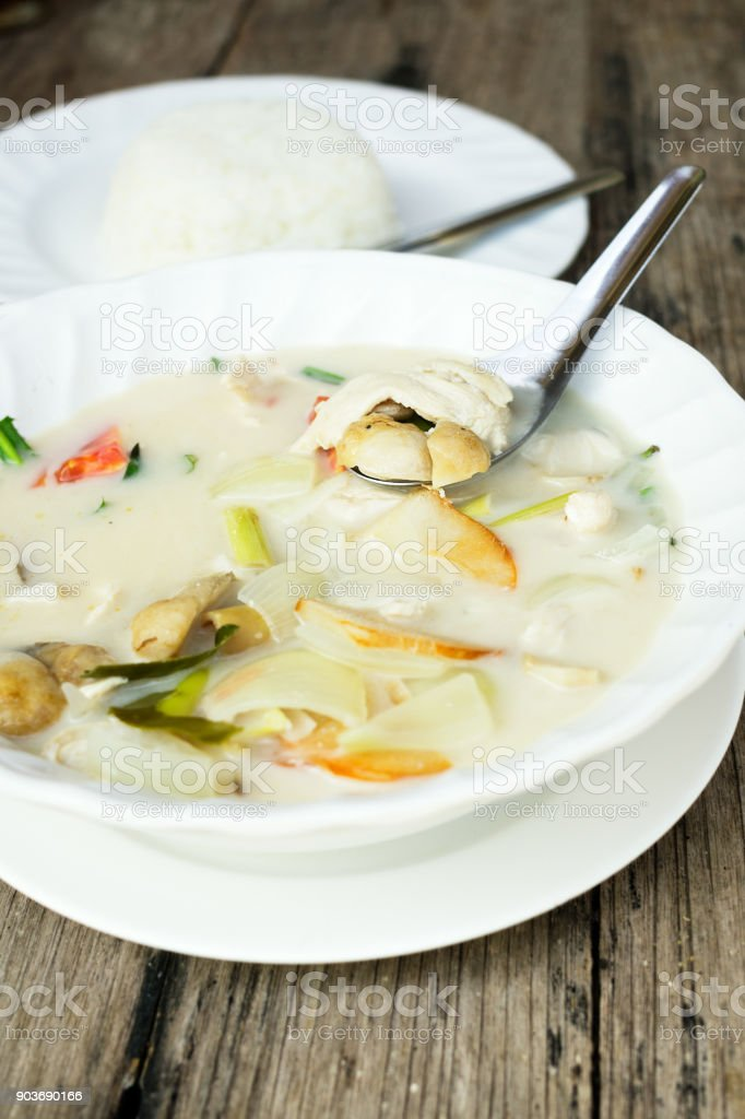 authentic Thai dinner background: Tom kha gai spicy soup, plain rice and pad kra pao with fried egg on top on wooden table at local cafe. Asian food concept stock photo