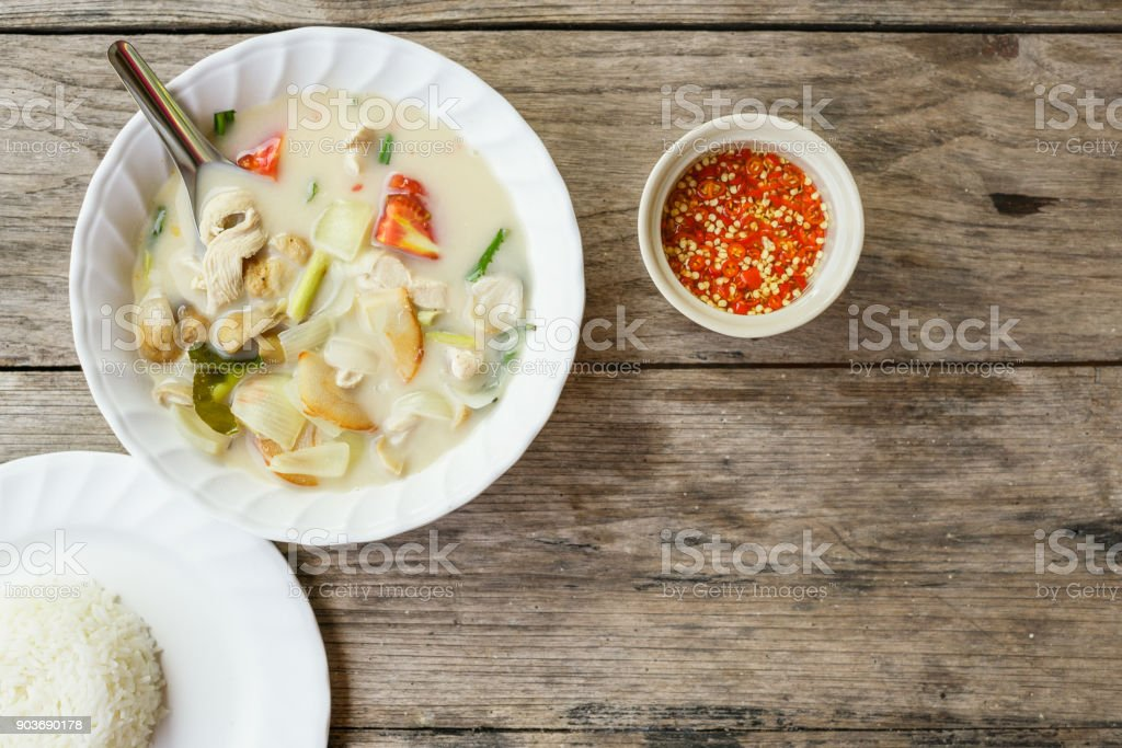 authentic Thai dinner background: Tom kha gai spicy soup, plain rice and pad kra pao with fried egg on top and homemade chilli sauce on wooden table at local cafe. Asian food concept stock photo