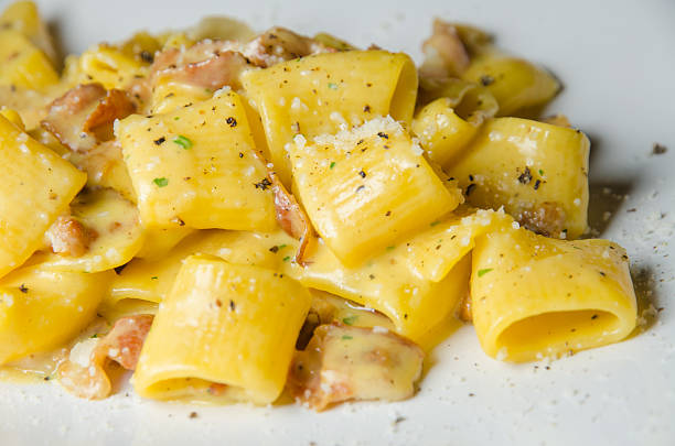 authentic traditional italian carbonara pasta with bacon and egg authentic traditional italian carbonara pasta with bacon and egg cream sauce rigatoni stock pictures, royalty-free photos & images