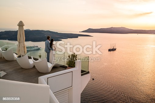istock Authentic Wealth - rich couple standing on terrace with amazing sea view 863505358