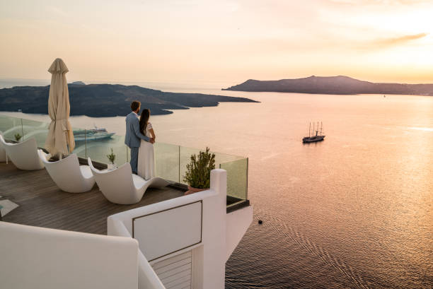 Authentic Wealth - rich couple standing on terrace with amazing sea view couple in love on romantic location - luxury hotel in greece overlooking the caldera of greek island santorini terrace with seaview vacation honeymoon high society stock pictures, royalty-free photos & images