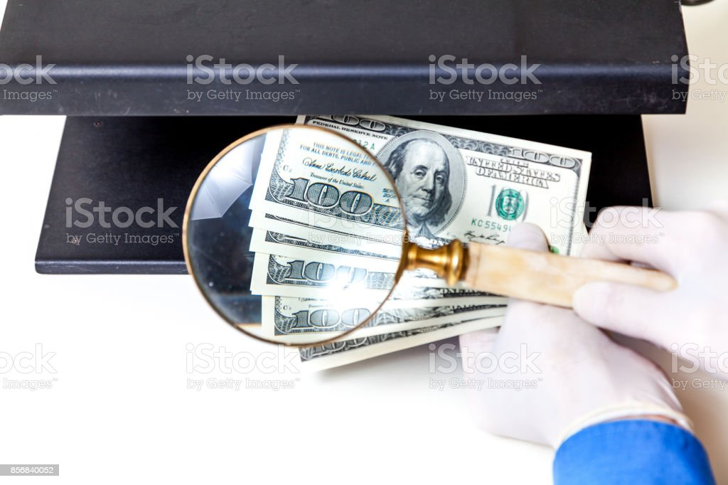 Authentication of banknotes using a magnifying glass stock photo