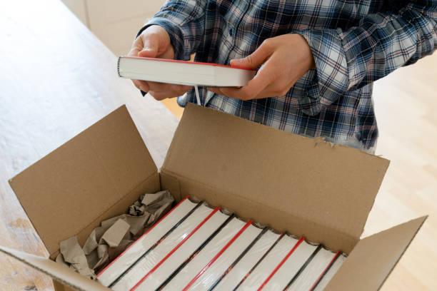 Autor öffnet Paket mit Proben ihres neuen Buches und überprüft die gebundene Ausgabe – Foto