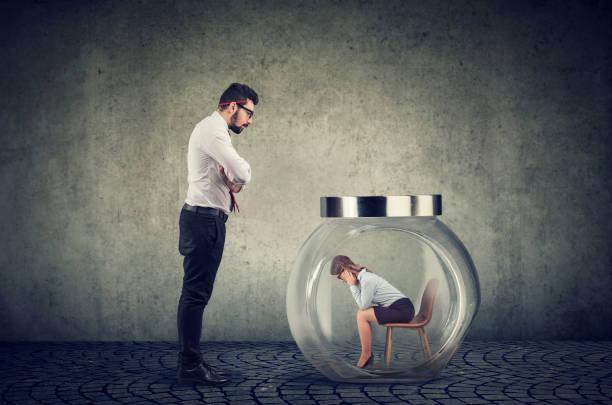 Empresario jefe autoritario mirando un frasco de vidrio con una mujer capturada dentro - foto de stock
