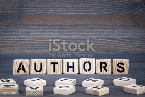 1018285596 istock photo Authors word written on wood block. Dark wood background with texture 697131278