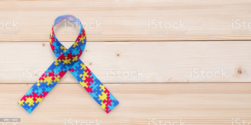 Autism awareness ribbon in puzzle or jigsaw pattern (isolated on wood background with clipping path) for World Autism Awareness day, mental health care concept for autistic child person support and family nursing care - Royalty-free Alertness Stock Photo