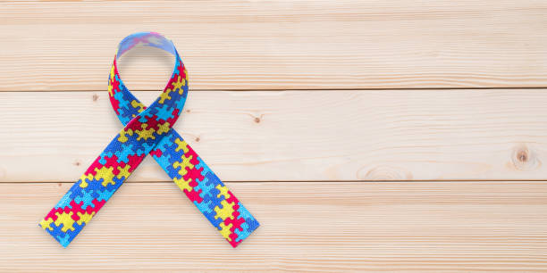Autism awareness ribbon in puzzle or jigsaw pattern (isolated on wood background with clipping path) for World Autism Awareness day, mental health care concept for autistic child person support and family nursing care stock photo