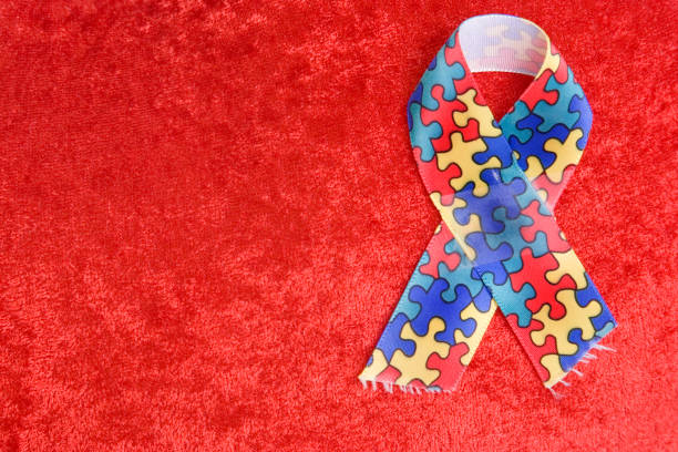 Autism ribbon on textured red background stock photo