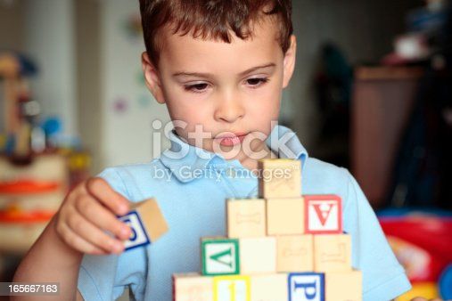 Child with autism deciding where is the best place to put his block. Shall he build it higher?