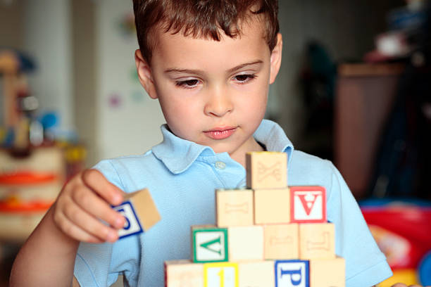 Autistic boy building with blocks stock photo