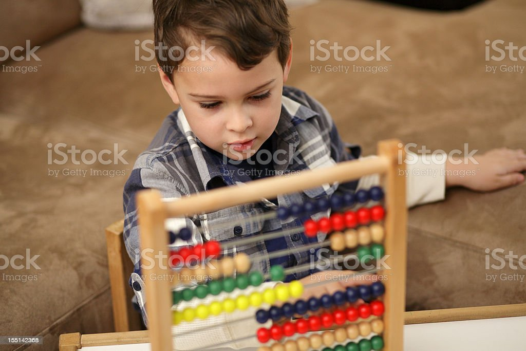 Autistic boy counting on his abacus stock photo