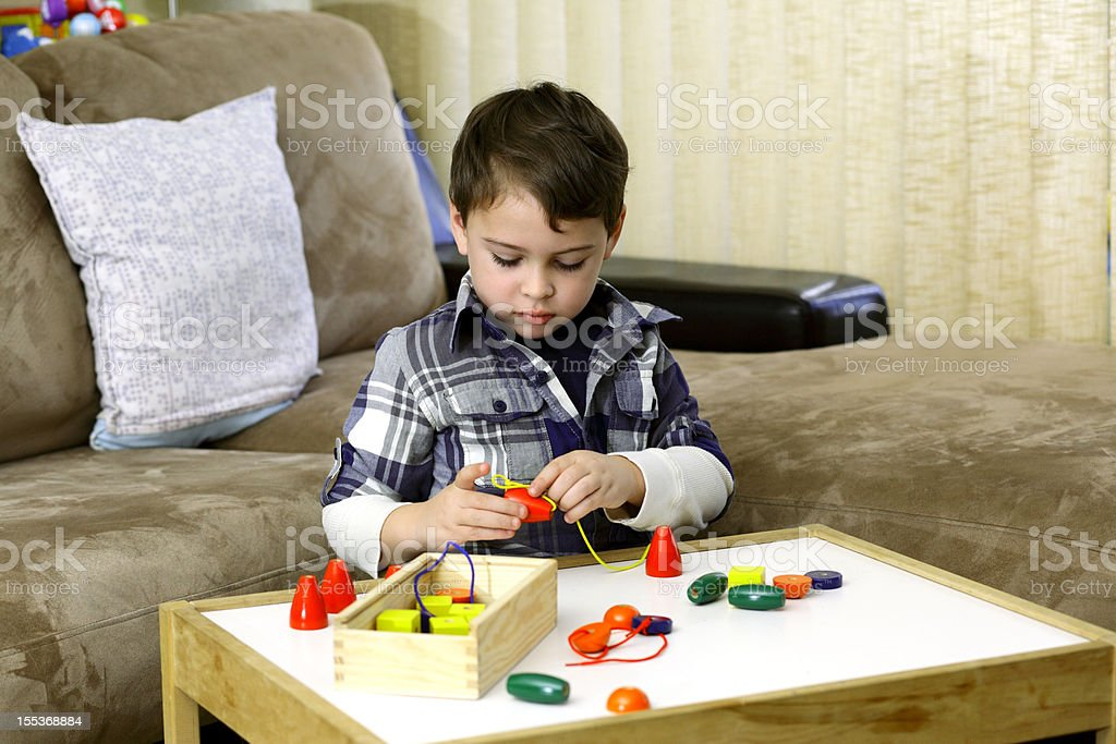 Autistic boy playing with colorful wooden beads royalty-free stock photo