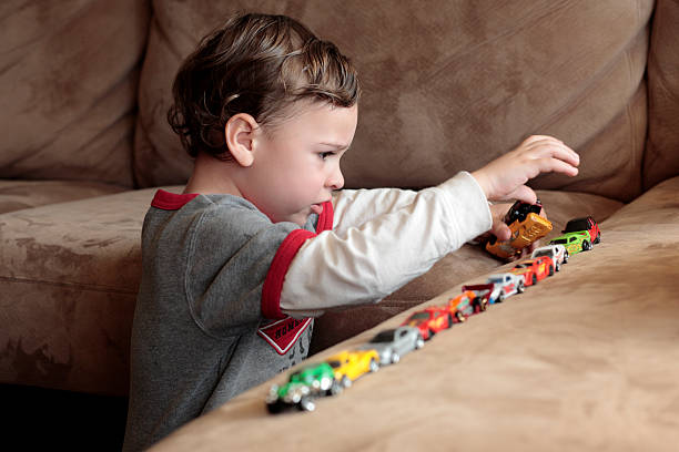 Autistic boy playing with toy cars Autistic boy lining up cars to achieve order in his world. autism stock pictures, royalty-free photos & images