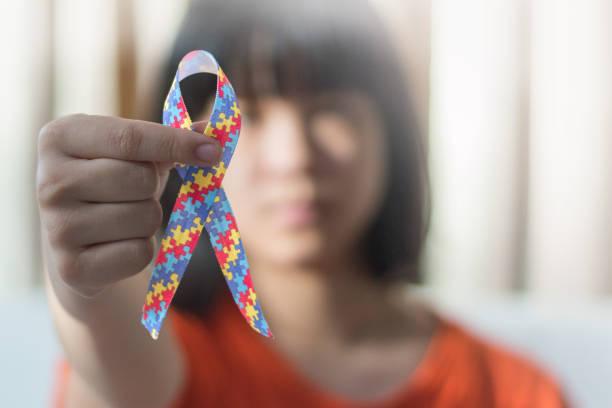 autistische kind mädchen halten band symbol von bunten puzzleteile zusammen für tag der sensibilisierung für menschen mit autismus spectrum disorder auf der ganzen welt. - autismus stock-fotos und bilder
