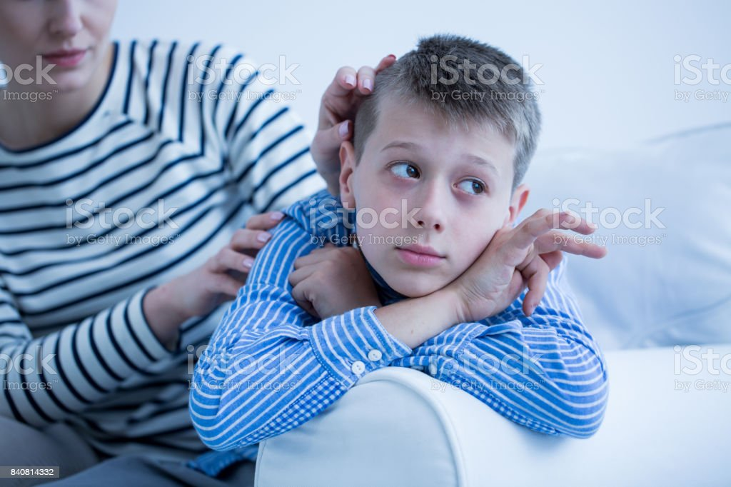 Autistic child lying on sofa stock photo
